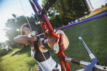 Attractive Female Practicing Archery At The Range. Focus Is On Bow